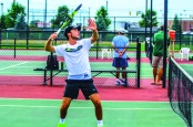 AT THE NET: Rodrigo Manzo, who earned all-conference honors for this Foresters this season, prepares to take an overhead stroke in a home match. (photo by Quinton Worthy)