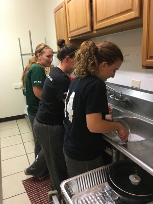 MEAL MINISTRY: Women's soccer players Jaime Calvin, Kat Highstead and Abby Field wash dishes after helping serve dinner at