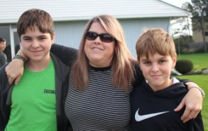 MOVING FORWARD: Zachary, 15, and Noah, 11, pose with their mother outside of their church before being dropped off for a weekend long retreat with their youth group. This outing is one of the first social events they have participated in since their father's death. (Photo by Katelynn Farley.)